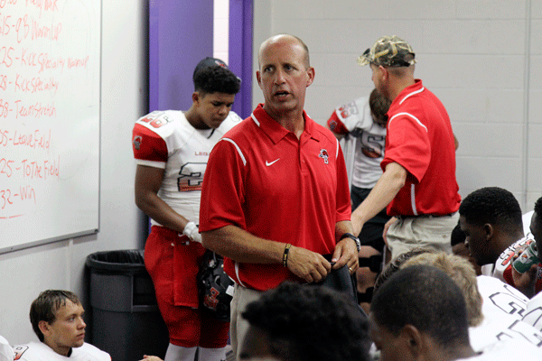 Head varsity football coach, Chris Melson, talks with the varsity team before a game. He won the class 3A Oklahoma high school state football game in 1986.