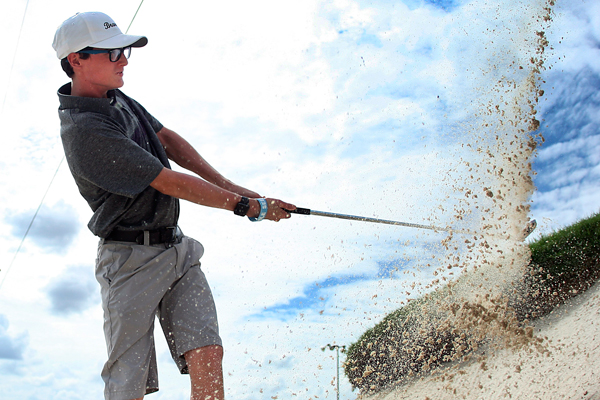 Kyle Pitts hits out of the bunker at golf practice.