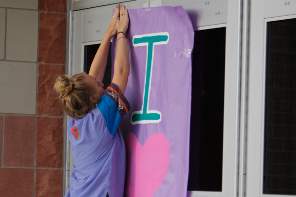 Student Body President, Sadie Johnson hangs a sign for the 80's dance.