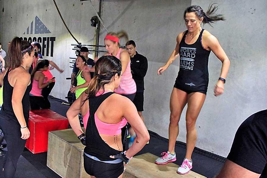 Lacy Beckler,  Legacy track and cross country coach, does box jumps during a crossfit workout.