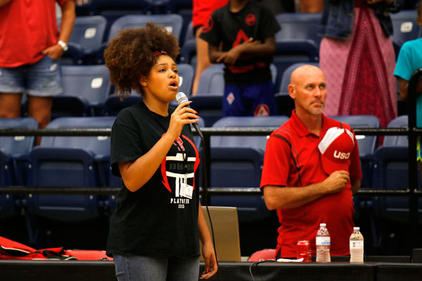 Nyah Buckrham, 12, sings the national anthem at a volleyball game.