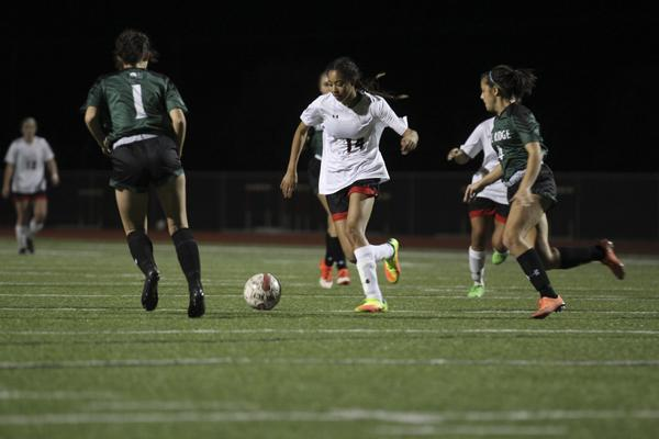 Senior Heaven Conner dribbles the ball through Lake Ridge defenders in a district game.