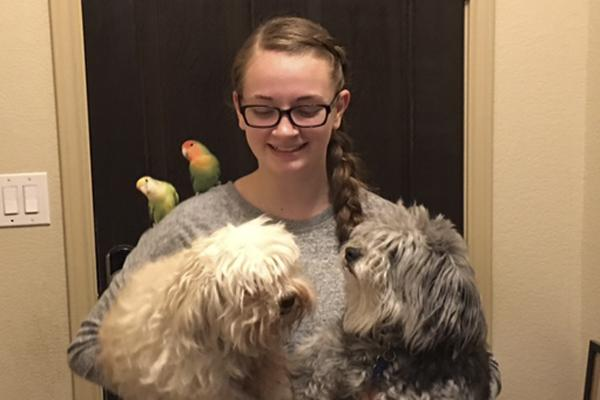 Brooke Blaine, 10, holds two of her dogs as her birds perch on her shoulder. Blaine owns 15 pets, including snakes, birds and dogs.