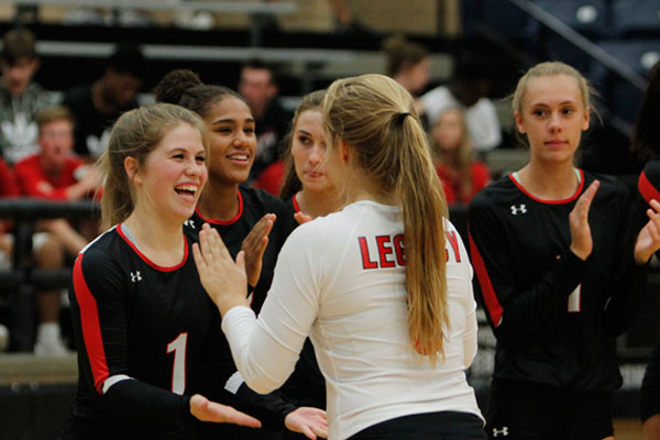 Senior Katelyn Allen cheers on her teammate before the start of the Varsity Volleyball match against Richland.