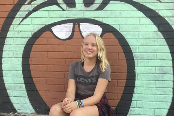 Zoe Menzel, 11, poses in front of a mural in downtown Mansfield.