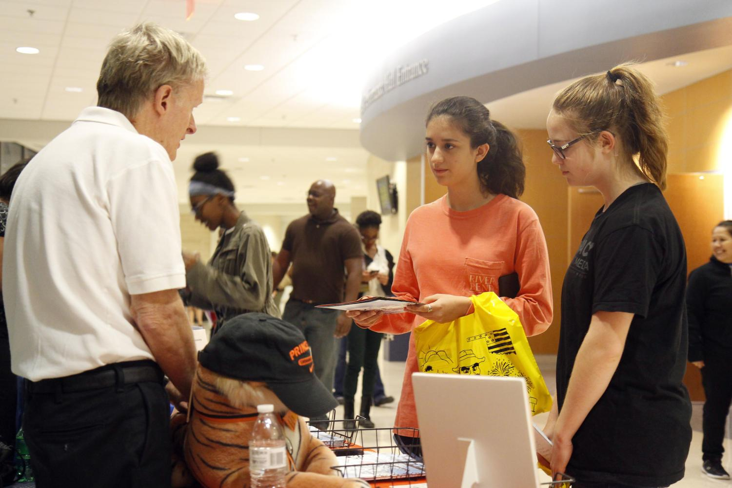 Sophomores Isabella Estes and Brinley Koenig speak with a college representative at College and Career night. The event was held at The Center to give students a chance to speak with admissions counselors from schools across Texas.