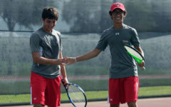 Junior Christian Violette smiles with his teammate at the varsity tennis match against Summit on Oct. 5.