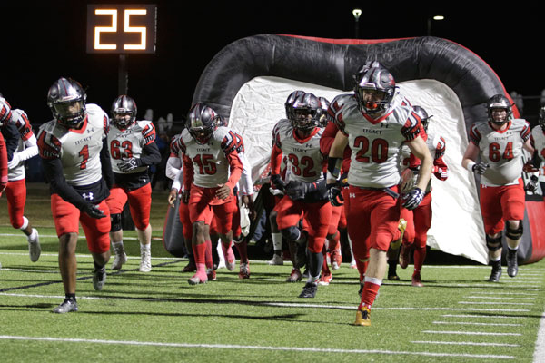 Senior Justin O'shields (#20)  runs out of the tunnel prior to varsity football's match against Lake Ridge on Oct. 27.  The first round of playoffs will be on Nov. 17.