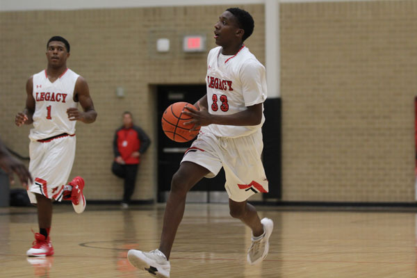 Junior Michael Simmons takes the ball down the court followed by teammate Jalen Catalon, 11 during last year's varsity match against Ennis on Dec. 12.