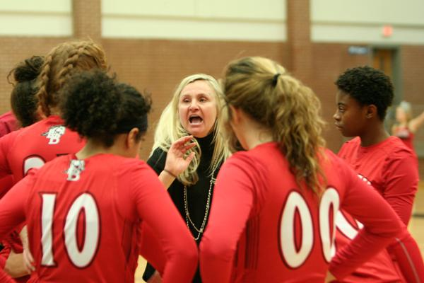 Head Coach Michelle Morris discusses plays with the girls varsity basketball team during their game against Summit.