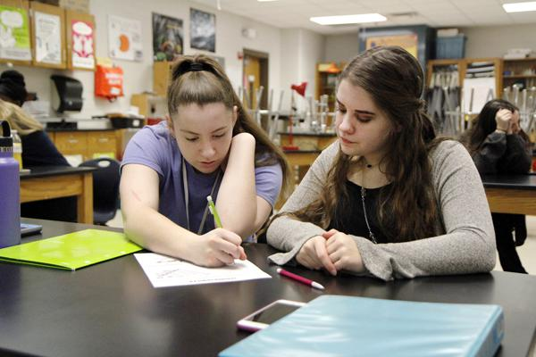 Lindsey Blakely, 12 and Katelyn Carney, 12 work on an assignment in AP Biology.