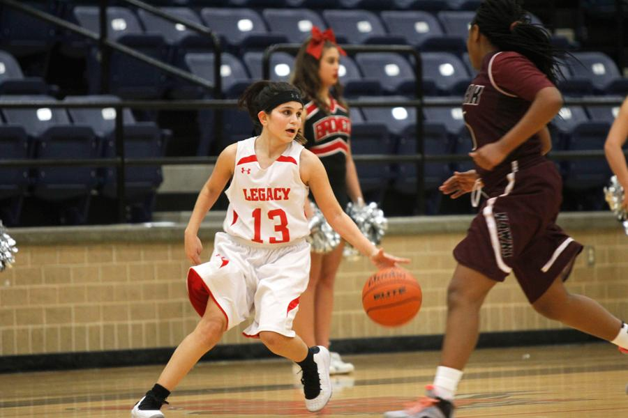 Sophomore Colleen Shaw dribbles down the court as she looks to a teammate to pass the ball to in the game against Red Oak.