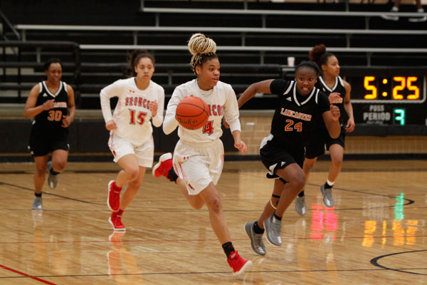 Harmoni Turner, 10, takes the ball down the court during the Broncos' match against Lancaster on Jan. 26.