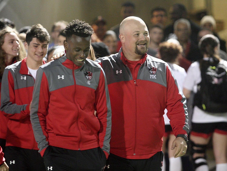Coach Michael Keel talks to Akim Bangwiha, 12, during a varsity soccer game.