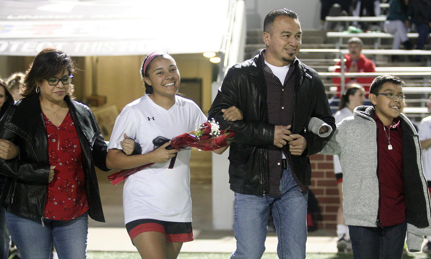 Senior Dezirae Rodriguez walks the field with her family on Senior Night.
