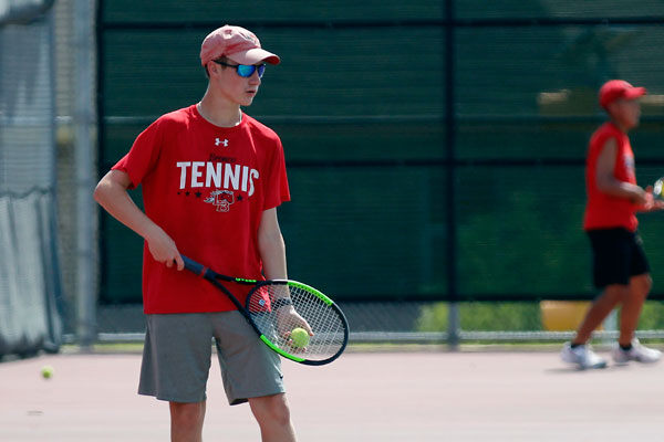 Noah Batson, 10, gets ready to serve during tennis practice.