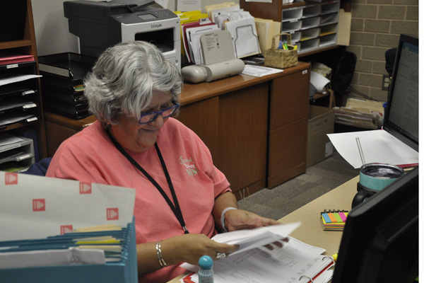 Secretary Lori Carbajal organizes paper in a binder for the counseling office.