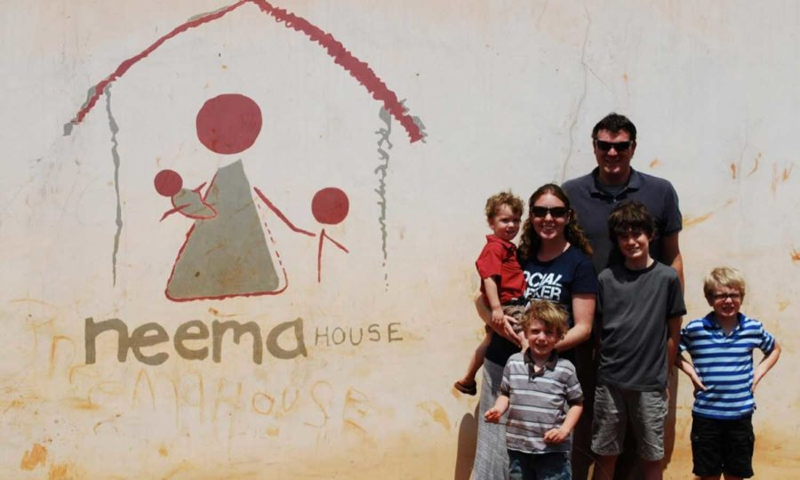 Mr. and Ms. McFaddin stand in front of a Neema House building  with their children.