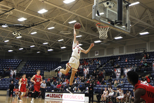 Matthew Reeves, 12, dunks the basketball in the fourth quarter of the varsity boys basketball game. Legacy beat Burleson High School, 63-45. (Conner Riley photo).