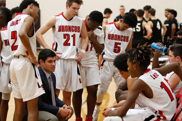 Coach+Joe+Martin+discusses+the+next+play+with+the+freshmen+boys+basketball+team.+%28Seth+Miller+photo%29