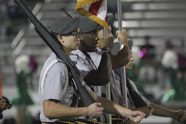 Carson Keeley and Soloman Davis, 12, present the colors at the football game against Bryan Adams