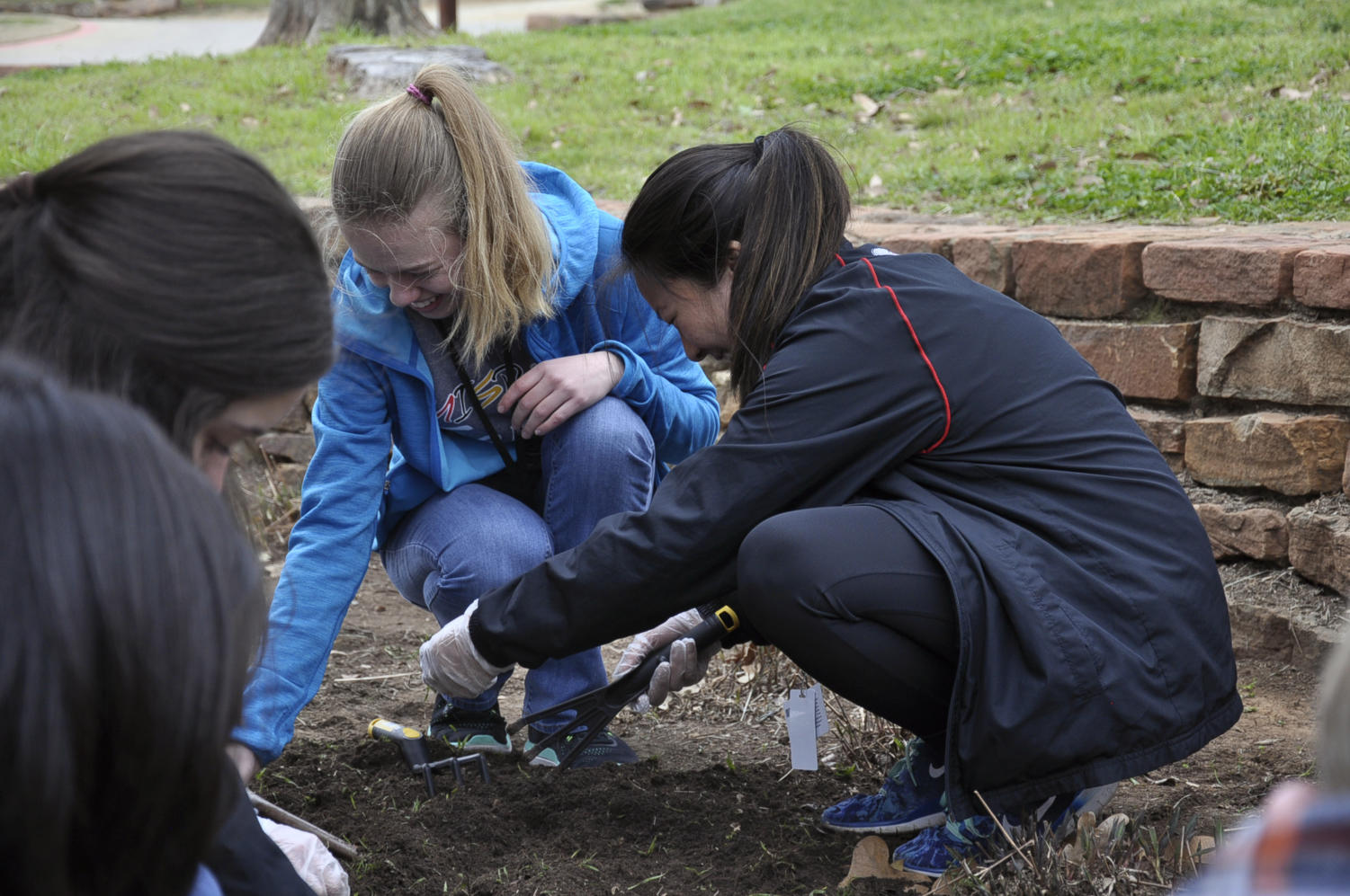 Spreading mulch, junior Megan Novak and senior Trinity Nguyen volunteer on the Day of Service on March 7.