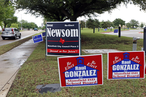 Passing cars view school board and city council election campaign signs outside of the Tarrant County Subcourt house at Mansfield on May 2.