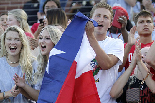 Ryan Betchel, 12, cheers holding a texas flag in the student section.