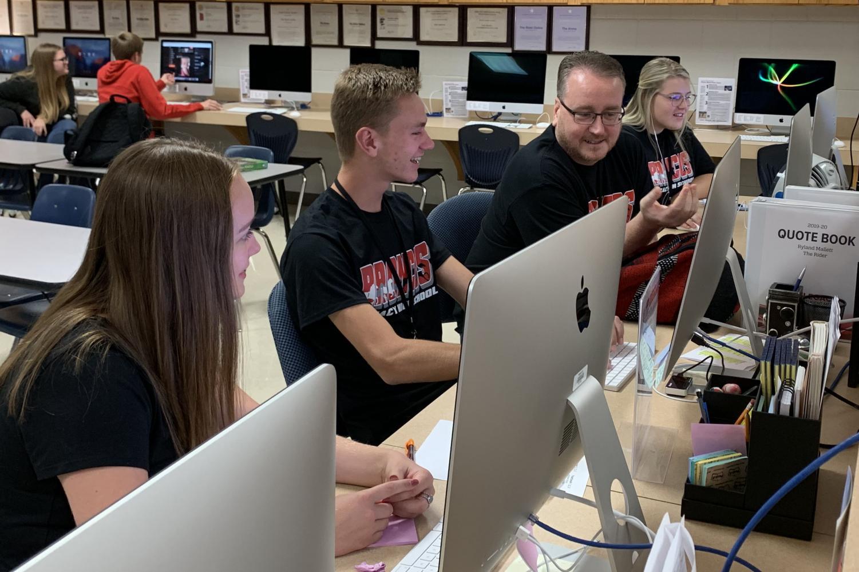 Mr. Leland Mallett assists editors Brinley Koenig, 12, and Ryland Mallett, 12, during the Newspaper class. Mallett will recieve the Journalism Educators Association's Medal of Merit this fall.