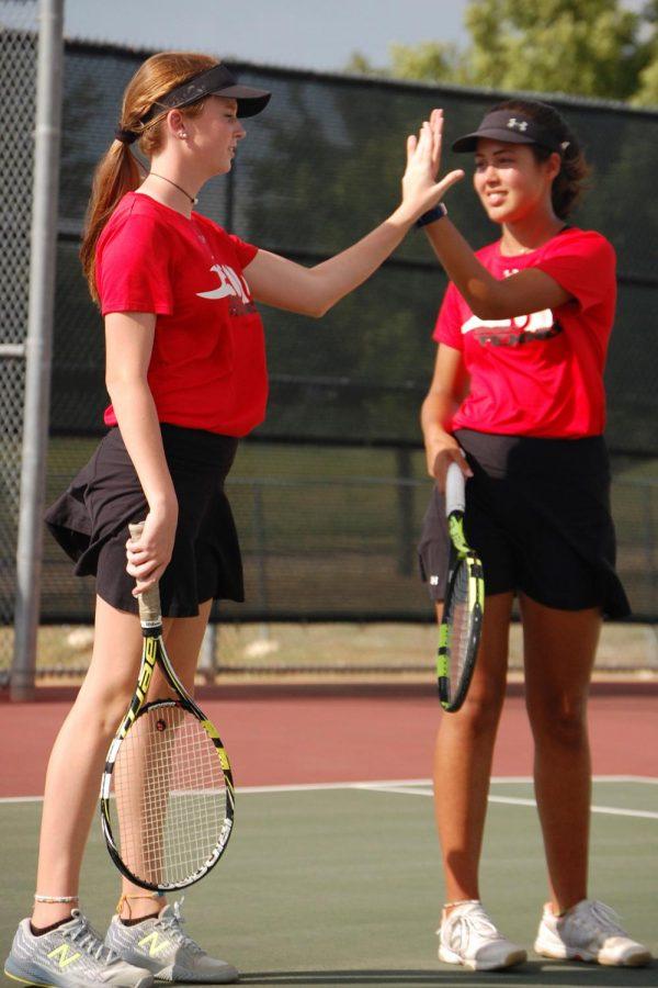 Varsity tennis players Abigail Carpenter, 11, Mia Retnam, 12, high five after scoring a point. (Brooklyn Hilmes photo)
