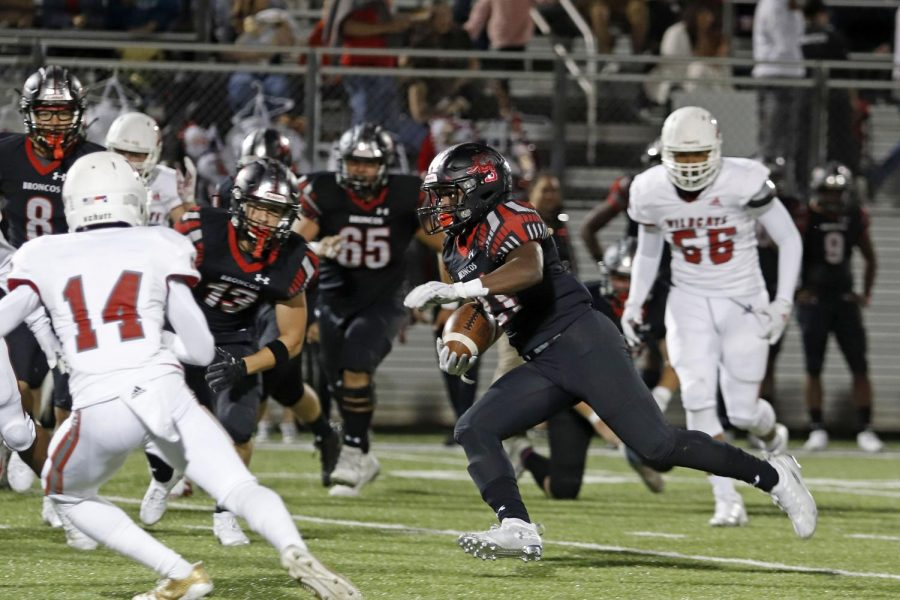 Senior Ayo Adeyi, 21, runs the ball during the Woodrow Wilson game. The Broncos won their first game of the season 35-7.