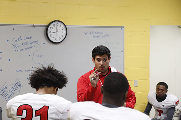 Coach Joe Martin discusses pre-game strategy with the football team prior to the game against Highland Park.