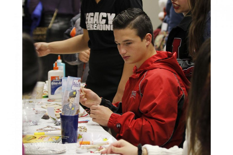 Beau Kilgore, 10, decorates Christmas ornaments at the Student Council booth during the Toys for Tots event.