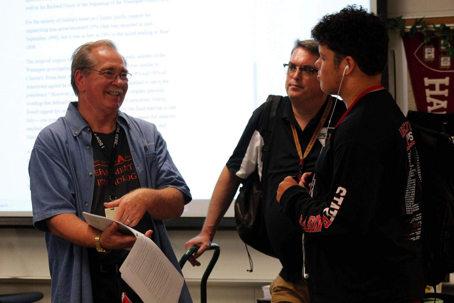 Debate sponsor Howard Ritz explains a case file to a student during practice.