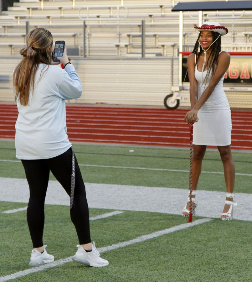 Senior Ja'Riah Giles gets her photo taken by assisstant director Miss Alexandria Thomas at the drill team sunrise ceremony Sept. 24. Giles was initiated as Senior Lieutenant and received her hat and baton for the 2020-2021 season.