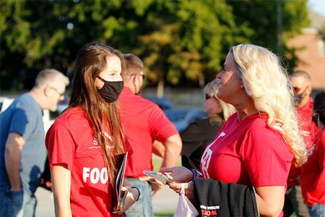 Student Council member, Casey Burkham, talks to a parent at the football game against Eaton High School.