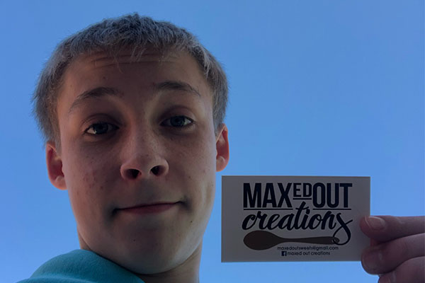 Sophomore Max Kociech takes a selfie with his business card from his self-made business.