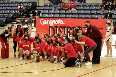 "The varsity girls basketball team poses for the district championship picture after claiming the championship for the first time in school history. ""We were ecstatic. We were so proud of the girls and all their hard work,"" Coach Jeremy Lyday said. (Amara Shanks Photo)"