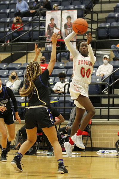 Coniah Cooley, 12, makes a jump shot toward the basket. The varsity girls basketball team completed the season undefeated making them eligible to play in the first-round playoff game. (Madison Moyer Photo)