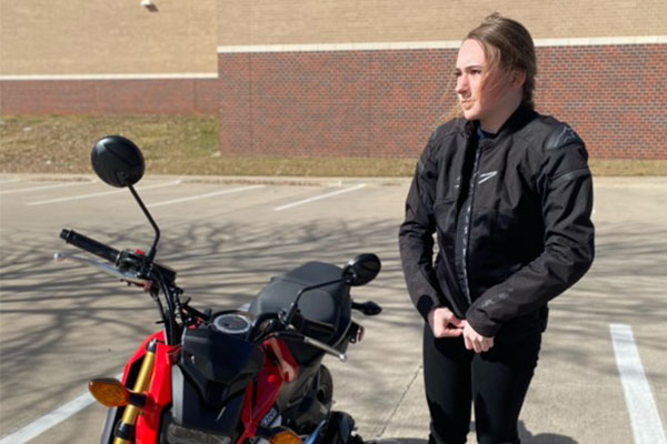 In the school parking lot, sophomore Della Duke prepares to ride her motorcycle home.