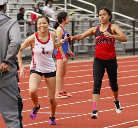 Sophomore Ariana Pacheco passes the baton to Leilani Fierro. (Madison Moyer Photo)
