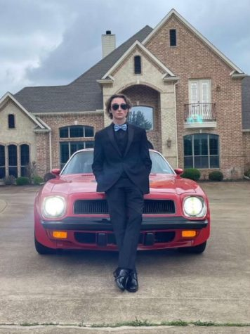 Senior Jay Smith stands in front of his car for a photo