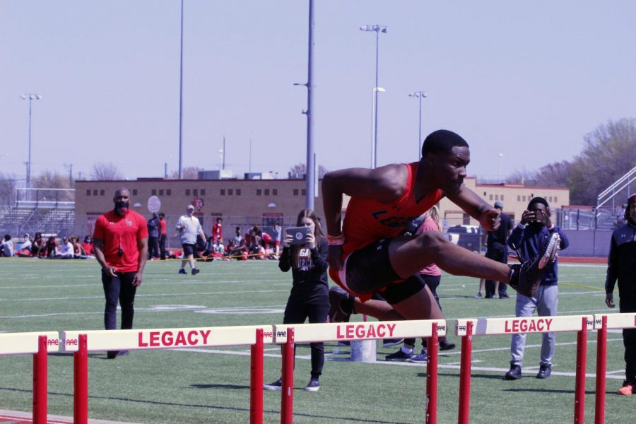 Cameron Bates jumps a hurdle as his dad, Coach Bates, observes