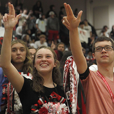 At the end of the homecoming pep rally, Mariah Hanlon, 10, and Connor Whitfill, 11, raise the Legacy L during the school song.
