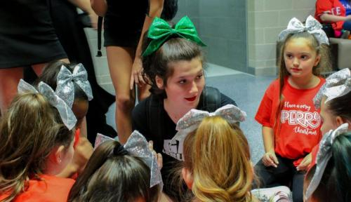 Darcie Phillips, 10, gives her elementary cheer club a pep talk before they perform at Toys for Tots.Teams and clubs from all over the district come to this event to perform routines that entertain the massive crowd. (Landri Hargrove Photo)