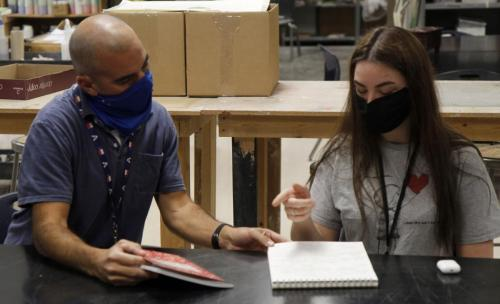 In Art 3 Ceramics, Catherine Walworth, 11, discusses ideas for the upcoming Sustained Investigation Project with teacher Mr. Shane Skinner. All in-person students and teachers must wear a face mask at all times throughout the day. (Avery Florence Photo)
