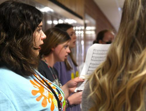 Isabel Lara, 12, practices with the varsity chamber choir as they work on rhythm and make sure notes are clean for two upcoming performances of the national anthem at the homecoming pep rally and the 9/11 ceremony. (Nicole Novak Photo)