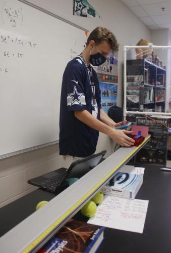 Andrew Bobe, 11, sets up a physics lab on graphing the motion of a car. AP Physics students constantly participate in labs to help students understand the material. (Nicole Novak Photo)
