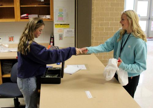 During advisory, Annelise Vinson, 10, works the StuCo store as students pay for Homecoming shirts. At all lunches, StuCo sells extra Homecoming shirts and allows students to pick up their pre-ordered shirts. (Catherine Walworth Photo)