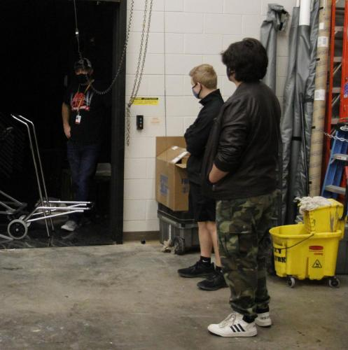 Mr. Ferman waits for two theater students to raise the door that connects the workshop and black box theater. They were cleaning out the workshop to get rid of props and background that wasn't needed. (Noah Dirnberger Photo)